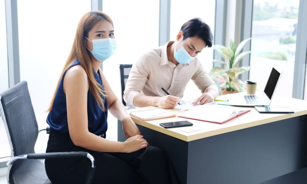 Woman and Man wearing masks during a meeting.