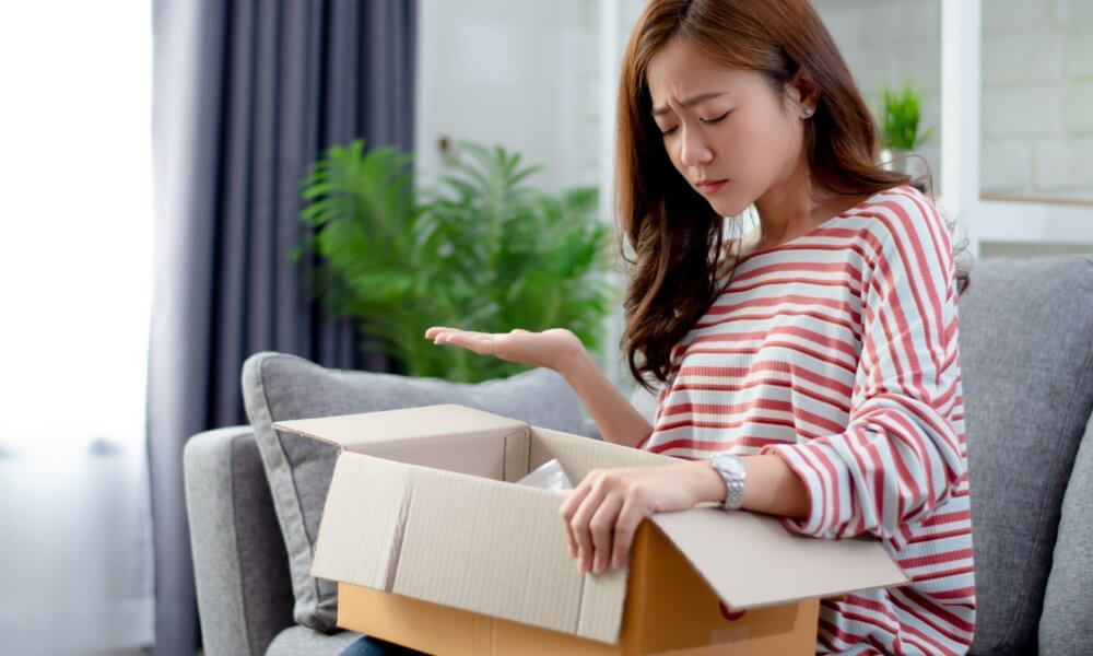 Woman opening up box to see the product is damaged